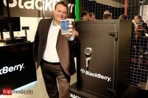 Blackberry Senior Manager, Technical Solutions Kai Schulte präsentiert den Hauptgewinn vor dem Tresor.