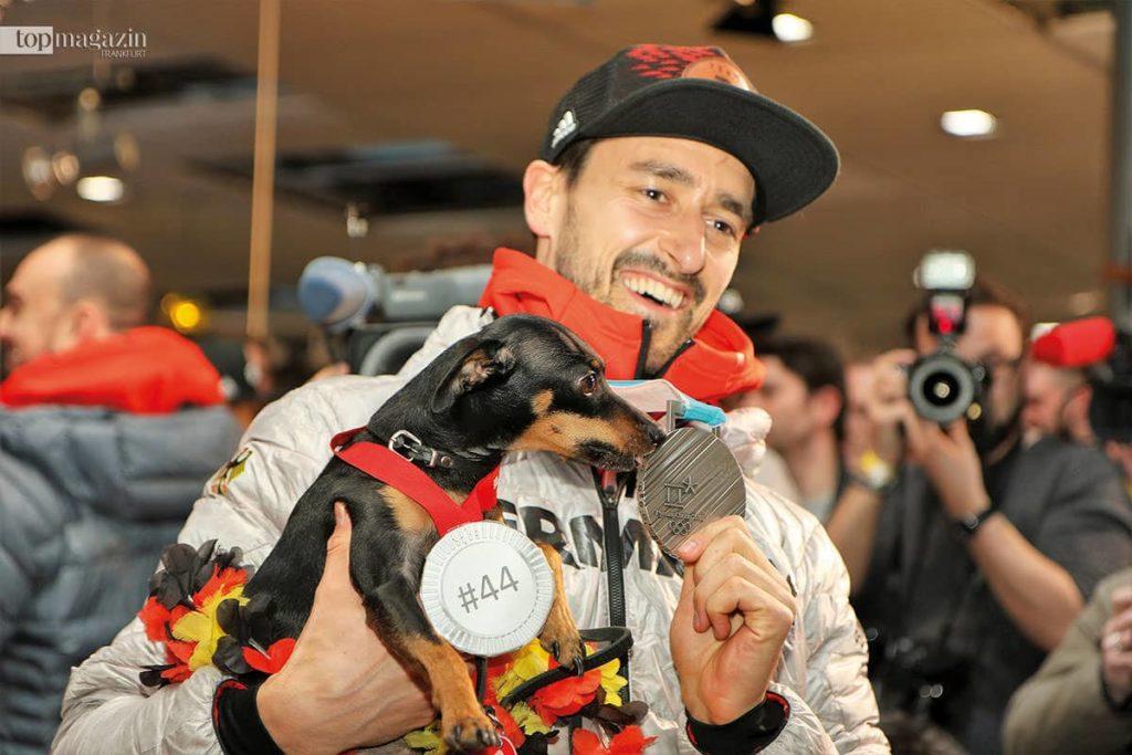 Eishockey-Spieler Dennis Endras präsentiert seinem Hund Kia stolz seine Silbermedaille.