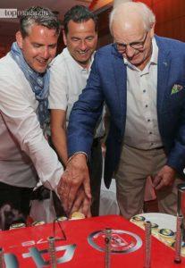 Ferrari-Club-Präsident Ben Dörrenberg schneidet mit seinen Vorgängern Horst Kespuhl und Arnold Gardemann die Geburtstagstorte an.