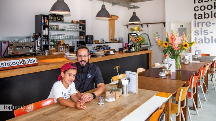Rachid Belhabib mit seinem Sohn Rayan an der sieben Meter langen Tafel im Rashcook Table