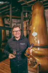 Andreas Thümmler mit seinem ersten Single Malt Whisky vor den imposanten Pot Stills